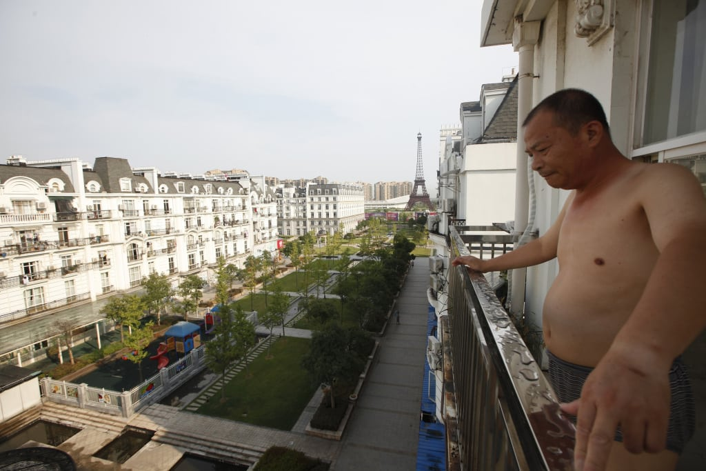 Resident stands on the balcony of his apartment at the Tianducheng development in Hangzhou