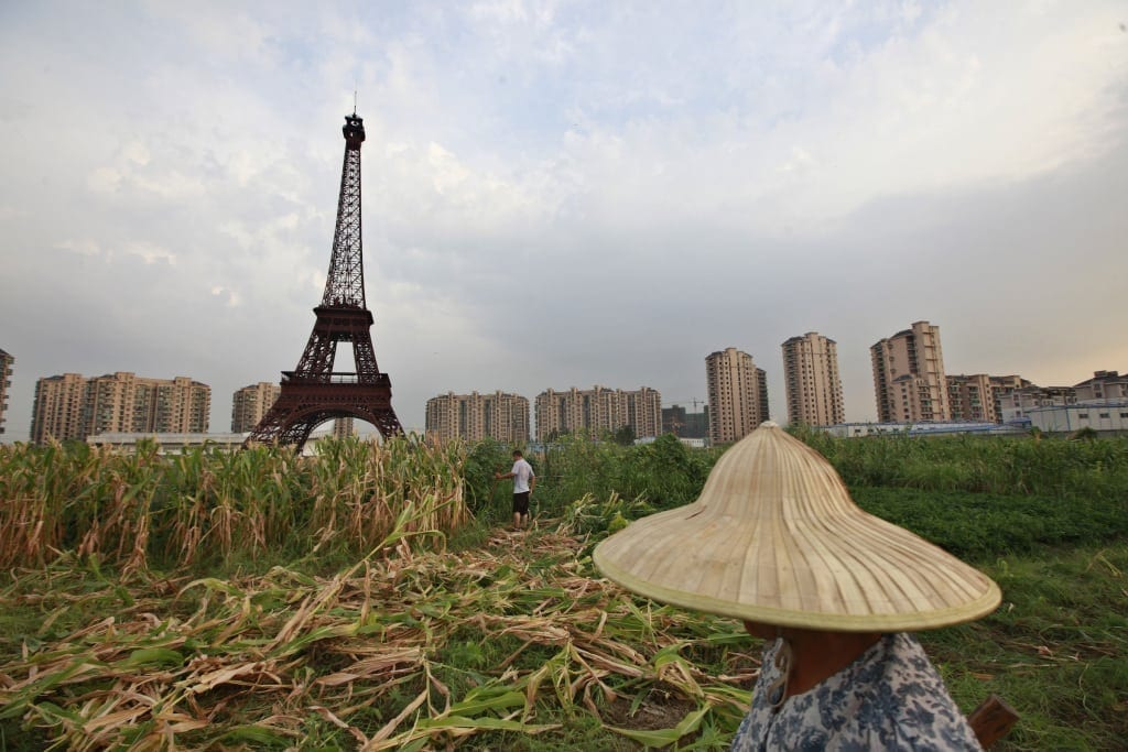 Farmer walks through field near a replica of the Eiffel Tower at the Tianducheng development in Hangzhou