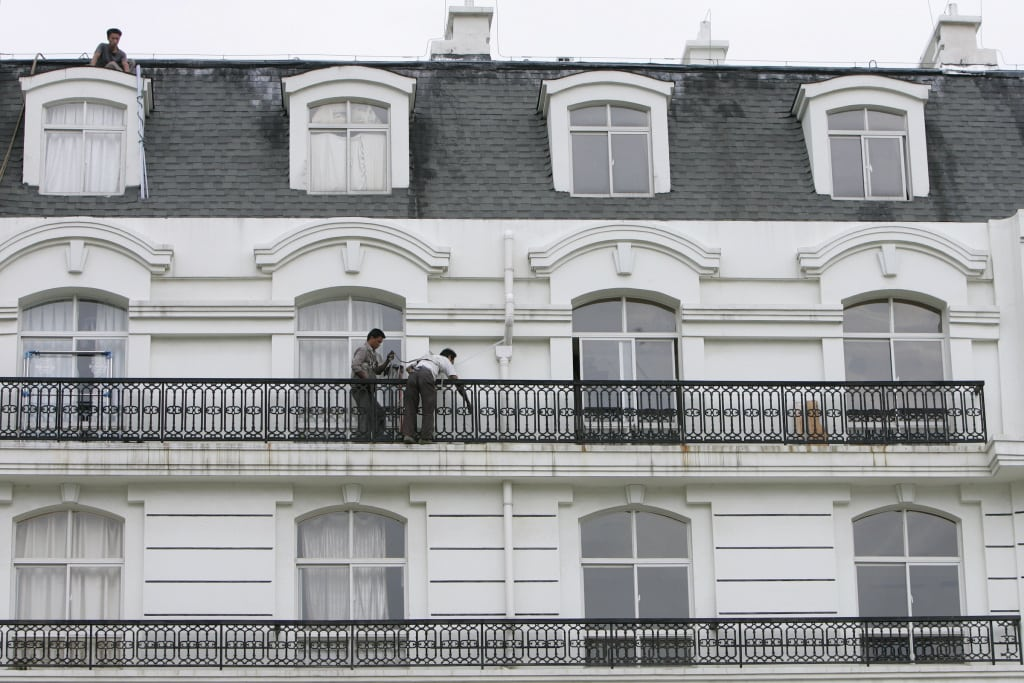 Workers stand in balcony outside apartment at Tianducheng, residential area on outskirts of Hangzhou in east China?s Zhejiang province