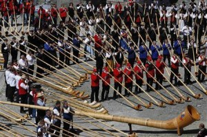 Alphorn players blow their instruments to break the world record for the largest ensemble of people playing the alphorn, on the Gornergrat in front of the Matterhorn mountain near Zermatt