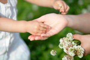 The child who hands a white clover to whose mother