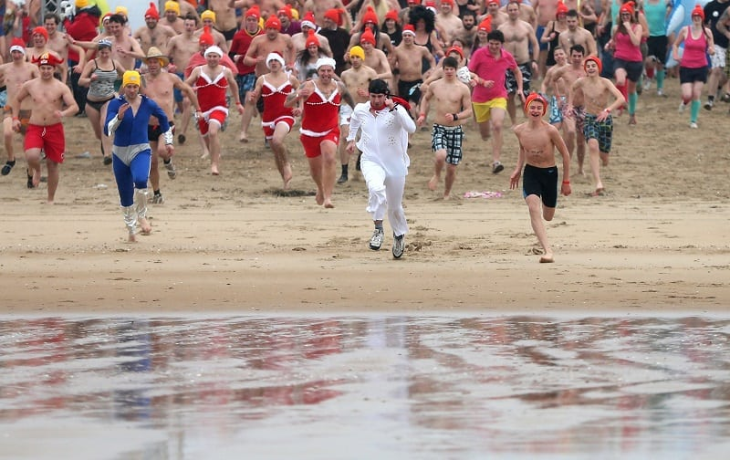 Participants run towards the waters of the North Sea during the annual New Year's swim event in Ostend